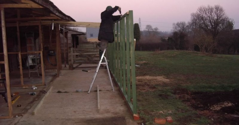 Before we could build the pens we had to lay a new concrete floor (thank you Mark and the boys). Unfortunately before we could lay the floor we had to cover the area to protect it from rain and frost. This picture shows Darren fixing a framework, which would become part of the cattery safety run and carry the new roof from the stable block.